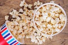 Popcorn in tazze di carta su superficie di legno Vista superiore Immagine Stock
