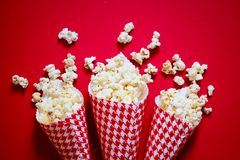 Popcorn. Three containers full on popcorn on a red background Royalty Free Stock Photography