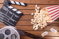 Popcorn tickets film roll and clapperboard on wooden table stock photos