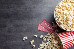 Popcorn and tickets on grey stone table, flat lay. Cinema snack