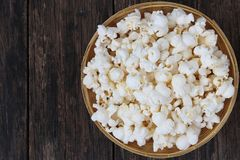 Popcorn top view. Popcorn in basket on wooden table close up royalty free stock photos