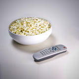 Popcorn and tv. Bowl of popcorn with remote control, tv addict concept stock photography