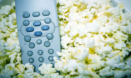 Popcorn and tv. Bowl of popcorn with remote control, tv addict concept Royalty Free Stock Photography