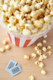 Popcorn and two cinema tickets. On wooden table taken from above Royalty Free Stock Images