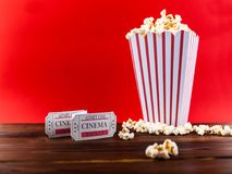 Popcorn With Two Red Movie Tickets. Red and White Bucket Of Popcorn With Two Red Movie Tickets/ Movie Night Close Up On Red Royalty Free Stock Photo