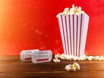 Popcorn With Two Red Movie Tickets. Red and White Bucket Of Popcorn With Two Red Movie Tickets/ Movie Night Close Up On Red Stock Photo