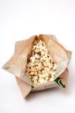 Popcorn in un sacco di carta su fondo bianco immagini stock