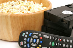 Popcorn & video w/remote control vhs. Shot of popcorn & video w/remote control vhs Royalty Free Stock Images