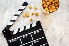 Popcorn voor het letten op FIM dichtbij clapperboard op grijze hoogste mening als achtergrond copyspace Stock Afbeeldingen