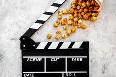 Popcorn voor het letten op FIM dichtbij clapperboard op grijze hoogste mening als achtergrond copyspace Stock Foto