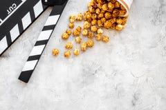Popcorn voor het letten op FIM dichtbij clapperboard op grijze hoogste mening als achtergrond copyspace Stock Foto's