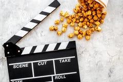 Popcorn voor het letten op FIM dichtbij clapperboard op grijze hoogste mening als achtergrond copyspace Royalty-vrije Stock Afbeeldingen