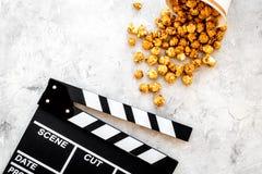 Popcorn voor het letten op FIM dichtbij clapperboard op grijze hoogste mening als achtergrond copyspace Stock Fotografie