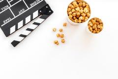 Popcorn voor het letten op FIM dichtbij clapperboard op witte hoogste mening als achtergrond copyspace Royalty-vrije Stock Afbeeldingen