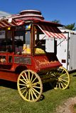Popcorn wagon offering bags of popped popcorn  for sale. Popcorn is for sale in an old decorated wood wheel coach which resemble a stagecoach Stock Images