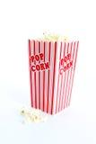 Popcorn on White Background. Red popcorn tub overflowing on white background stock photo