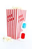 Popcorn on White Background. Red popcorn tub overflowing on white background stock photography