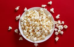 Popcorn in a white bowl against red background royalty free stock photography