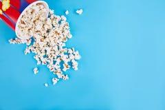 Popcorn wird auf einen blauen Hintergrund zerstreut Leerer Platz für Text stockbild