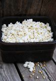 Popcorn on wood in basket. Handful of flavoured popcorn on brown wood tray with kernels accent Royalty Free Stock Photography