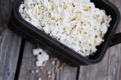 Popcorn on wood in basket on wood. Handful of flavoured popcorn on brown wood tray with kernels accent Stock Photos