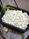Popcorn on wood serving tray in basket. Handful of flavoured popcorn on brown wood tray with dill accent Royalty Free Stock Photography