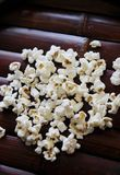 Popcorn on wood serving tray. Handful of flavoured popcorn on brown wood tray Stock Photo