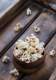 Popcorn in a wooden plate on the background Stock Images
