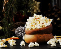 Popcorn in a wooden plate on the background of Christmas Stock Images