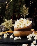 Popcorn in a wooden plate on the background of Christmas Stock Photo