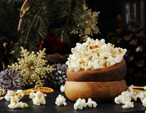 Popcorn in a wooden plate on the background of Christmas Stock Photos
