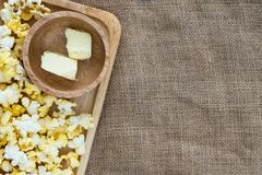Popcorn on wooden plate with butter in wooden bowl on gunny sack cloth. Top view, with copy space Stock Image