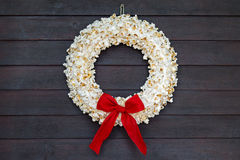 Popcorn wreath. With red bow hanging on dark wooden door Royalty Free Stock Images