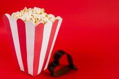 Popcornask på röd bakgrund och film i form av hjärta med utrymme för text royaltyfri fotografi
