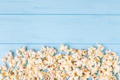 Popcornhorisontalbaner Röd avriven pappers- kopp och kärnor som ligger på blå träbakgrund kopiera avstånd Top beskådar arkivbilder