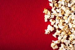 Popcornpopcorn op rode geweven dichte omhooggaande macro als achtergrond Stock Foto