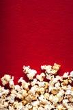 Popcornpopcorn op rode geweven dichte omhooggaande macro als achtergrond Royalty-vrije Stock Afbeelding