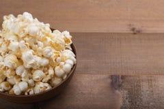 Popcornschüssel auf hölzernem Lizenzfreie Stockfotos