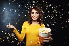 Popcornstrid Frineds som har det roliga hemmastadda partiet som kastar popcorn Royaltyfri Bild