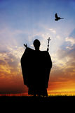 Pope silhouette. And dove at sunset Stock Photography