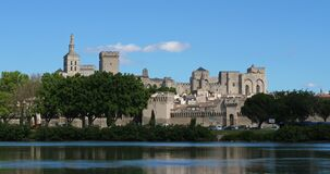 The Popes` Palace, Avignon, Vaucluse department, France. In the foreground is the river Rhone.