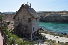 Popeye Village, filmset family park, island Malta. Popeye Village, popular filmset actual family park on Malta in Mediterranean sea. Coast under cliff and wooden royalty free stock photos