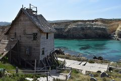 Popeye Village, filmset family park, island Malta. Popeye Village, popular filmset actual family park on Malta in Mediterranean sea. Coast under cliff and wooden royalty free stock image