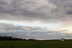 Popielaci chmura nadmiar pole z pojedynczym domem obraz royalty free