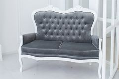 Popielata kanapa na białym ściennym tle Zdjęcie Stock