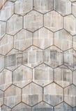 Popielatego wieloboka heksagonalny wzór na starej wyginającej się betonowy blok zewnętrznej ścianie zdjęcie royalty free