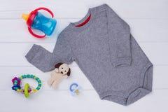 Popielaty dziecka onesie, zabawki i zdjęcia stock