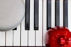 popielaty elegancki mówca i czerwień granatowiec na czarny i biały pianino kluczach na odgórnym widoku fotografia stock