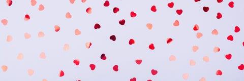 Popielaty tło z czerwonymi błyskotliwości serca confetti Walentynki C Obrazy Stock
