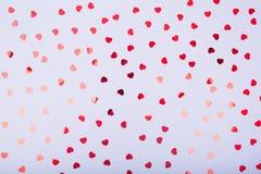 Popielaty tło z czerwonymi błyskotliwości serca confetti Walentynki C Zdjęcie Royalty Free